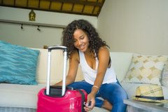 Young attractive and happy black latin American woman at home with suitcase sitting on sofa couch leaving for holidays trip feelin. G excited smiling cheerful in royalty free stock image