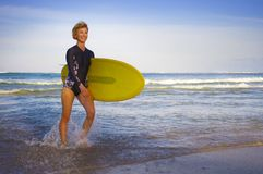 Young attractive and happy blonde surfer girl in beautiful beach carrying yellow surf board walking out of the water enjoying summ. Er holidays at tropical stock photos