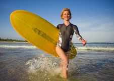 Young attractive and happy blonde surfer woman in beautiful beach carrying yellow surf board walking out of sea enjoying summer ho. Young attractive and happy royalty free stock image