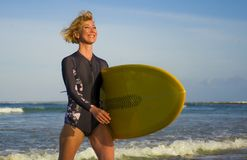 Young attractive and happy blonde surfer woman in beautiful beach carrying yellow surf board walking out of sea enjoying summer ho. Young attractive and happy stock images