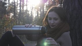 Young attractive happy brunette woman traveler in cozy warm sweater and scarf pouring hot tea from thermos in fall forest at sunse. T stock video footage