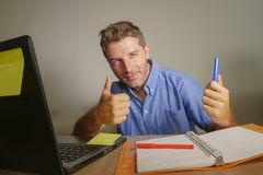 Young attractive and happy business man working at home office smiling confident and positive in successful work concept giving th. Umb up for okay and agreement royalty free stock images