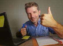 Young attractive and happy business man working at home office smiling confident and positive in successful work concept giving th. Umb up for okay and agreement stock image