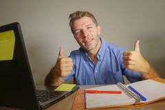 Young attractive and happy business man working at home office smiling confident and positive in successful work concept giving th. Umb up for okay and agreement royalty free stock photography