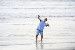 Young attractive and happy Caucasian 30s man having fun at Asian beach taking selfie picture with mobile phone smiling excited in stock photography