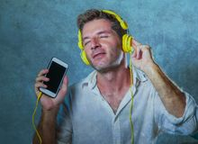 Young attractive and happy cool man listening to music song with yellow headphones using internet mobile phone dancing in trance s. Inging groovy and excited  on Royalty Free Stock Photo