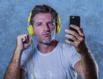 Young attractive and happy cool man listening to music song with. Yellow headphones using internet mobile phone dancing in trance singing groovy and excited  on Stock Photo