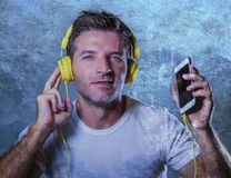 Young attractive and happy cool man listening to music song with. Yellow headphones using internet mobile phone dancing in trance acting groovy and excited  on Stock Image