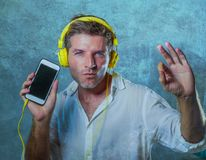 Young attractive and happy cool man listening to music song with. Yellow headphones using internet mobile phone dancing in trance acting groovy and excited  on Stock Photography