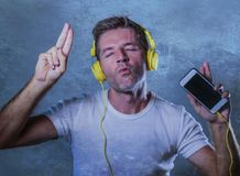 Young attractive and happy cool man listening to music song with. Yellow headphones using internet mobile phone dancing in trance acting groovy and excited  on Stock Images