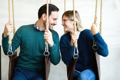Young attractive couple on date relaxing in swing stock image