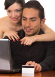 Young attractive happy couple in front of computer Stock Image