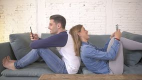 Young attractive and happy couple using internet app on mobile phone enjoying and laughing together sitting back to back at home c stock images