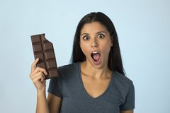 Young attractive and happy hispanic woman in blue top smiling excited eating chocolate bar  background Royalty Free Stock Photo