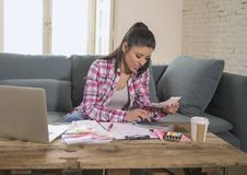 Young attractive and happy hispanic woman checking bills bank papers expenses and monthly payments smiling at apartment living roo. M couch in domestic finance Royalty Free Stock Images