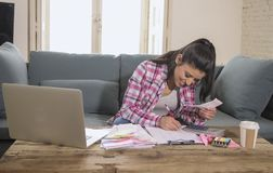 Young attractive and happy hispanic woman checking bills bank papers expenses and monthly payments smiling at apartment living roo. M couch in domestic finance Royalty Free Stock Image