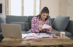Young attractive and happy hispanic woman checking bills bank papers expenses and monthly payments smiling at apartment living roo. M couch in domestic finance Stock Images