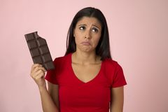 Attractive and happy hispanic woman in red top feeling guilty holding chocolate bar on pink background. Young attractive and happy hispanic woman in red top Royalty Free Stock Images