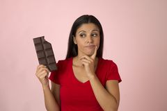 Attractive and happy hispanic woman in red top thinking and doubting holding chocolate bar on pink background. Young attractive and happy hispanic woman in red royalty free stock photo