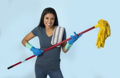 Young attractive happy Latin woman in washing gloves holding mop having fun singing and playing air guitar excited. And cheerful isolated on blue background in Stock Image
