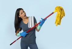Young attractive happy Latin woman in washing gloves holding mop having fun singing and playing air guitar excited. And cheerful on blue background in house royalty free stock photos