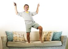Young attractive and happy man with headphones and mobile phone listening to music jumped on sofa couch dancing and singing crazy. Excited feeling in trace Royalty Free Stock Photos