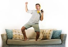 Young attractive and happy man with headphones and mobile phone listening to music jumped on sofa couch dancing and singing crazy. Excited feeling in trace Royalty Free Stock Images