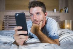 Young attractive and happy man lying on bed using internet mobile phone smiling sending text in social media and cellular communic. Ation addiction concept Stock Photo