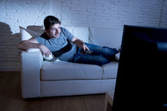 Young attractive happy man  lying on couch at living room watching excited tv holding remote control Royalty Free Stock Photo