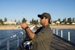 Young attractive and happy man in shirt and hat fishing at beach sea dock using fish road enjoying weekend hobby in holidays. And relaxing tourism concept Royalty Free Stock Images
