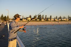 Young attractive and happy man in shirt and hat fishing at beach sea dock using fish road enjoying weekend hobby in holidays. And relaxing tourism concept Stock Photo