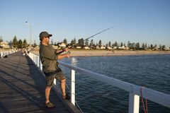 Young attractive and happy man in shirt and hat fishing at beach sea dock using fish road enjoying weekend hobby in holidays. And relaxing tourism concept Stock Photos