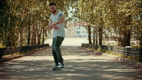 Young attractive happy man with tattoos performing dancing in the park and enjoying himself - buildings on the. Background. Mid shot stock video footage