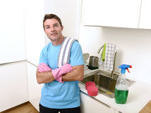 Young attractive and happy man washing with detergent spray bottle and sponge wearing gloves. Young attractive and happy man washing with detergent spray bottle royalty free stock photography