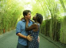 Young attractive and happy mixed ethnicity couple cuddling outdoors with attractive black afro American girfriend or wife and stock photos