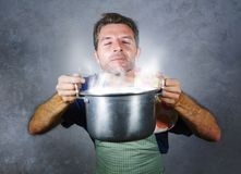 Young attractive happy and proud home cook man cooking soup holding kitchen pot smelling the meal aroma gesturing delighted and sa. Tisfied on isolated stock photography