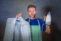Young attractive happy and proud house husband or single man holding iron showing shirt after ironing on studio backgroun stock photo