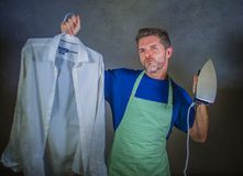 Young attractive happy and proud house husband or single man holding iron showing shirt after ironing on studio backgroun. D in domestic work male skills and Royalty Free Stock Photo