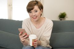 Young attractive and happy red hair woman sitting at home sofa c Royalty Free Stock Photography