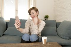 Young attractive and happy red hair woman sitting at home sofa couch drinking coffee taking selfie picture with mobile phone. Camera in internet social media Royalty Free Stock Image