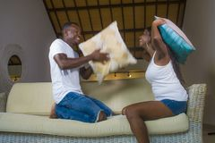 Young attractive and happy romantic afro American couple in love playful at living room couch playing pillow fight enjoying royalty free stock images
