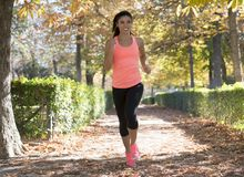 Attractive and happy runner woman in Autumn sportswear running a Stock Images