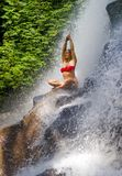 Young attractive and happy 30s woman with fit body practicing yoga wet under tropical paradise waterfall stream in meditation and. Young attractive and happy 30s stock photography