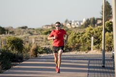 Young attractive and happy sport runner man with fit and strong healthy body training on off road track in Summer running workout. Under Summer sun in health Royalty Free Stock Image