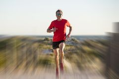 Young attractive and happy sport runner man with fit and strong healthy body training on off road track in Summer running workout. Under Summer sun in health Royalty Free Stock Photography