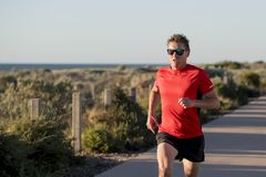 Young attractive and happy sport runner man with fit and strong healthy body training on off road track in Summer running workout. Under Summer sun in health Stock Images