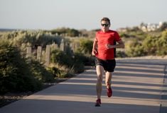 Young attractive and happy sport runner man with fit and strong healthy body training on off road track in Summer running workout. Under Summer sun in health Royalty Free Stock Photos