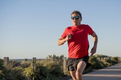 Young attractive and happy sport runner man with fit and strong healthy body training on off road track in Summer running workout. Under Summer sun in health Stock Photography