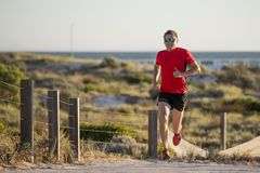 Young attractive and happy sport runner man with fit and strong healthy body training on off road track in Summer running workout. Under Summer sun in health Royalty Free Stock Photo