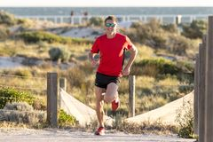 Young attractive and happy sport runner man with fit and strong healthy body training on off road track in Summer running workout. Under Summer sun in health Royalty Free Stock Images